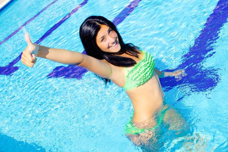 站立在游泳池微笑的逗人喜爱的好标志的愉快的妇女 免版税库存照片