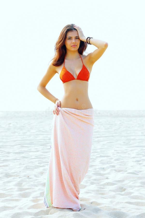 站立在游泳衣的海滩的美丽的妇女 免版税库存照片