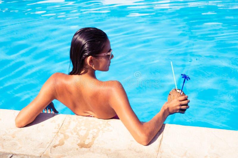 站立在游泳水池的妇女的后面看法画象 库存图片