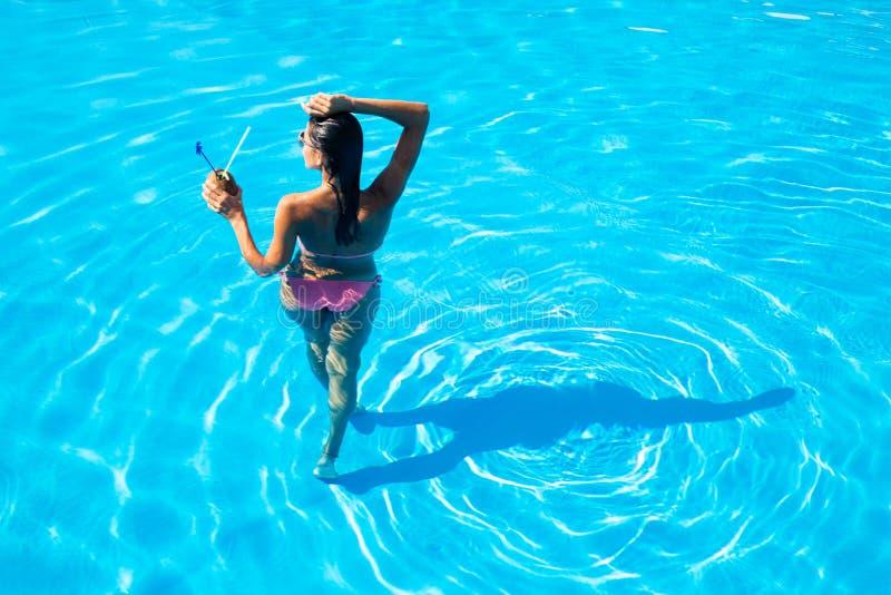 站立在游泳水池的妇女的后面看法画象 免版税库存图片