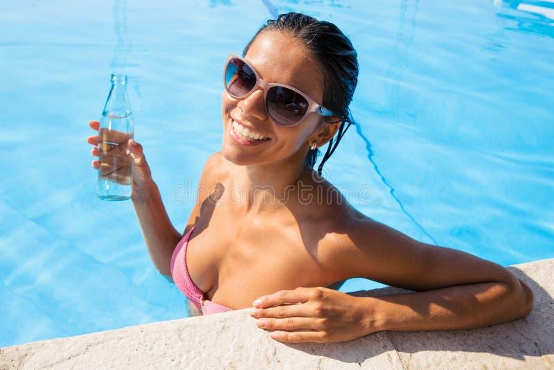 站立在游泳水池的妇女 免版税库存照片