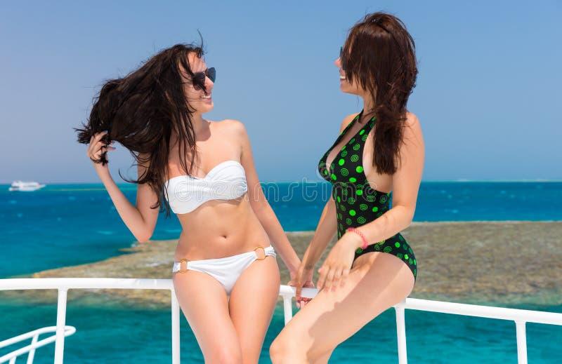 站立在游艇的泳装的美丽的女孩在太阳 免版税库存照片