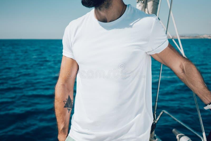 站立在游艇的年轻有胡子的人照片和 免版税库存照片