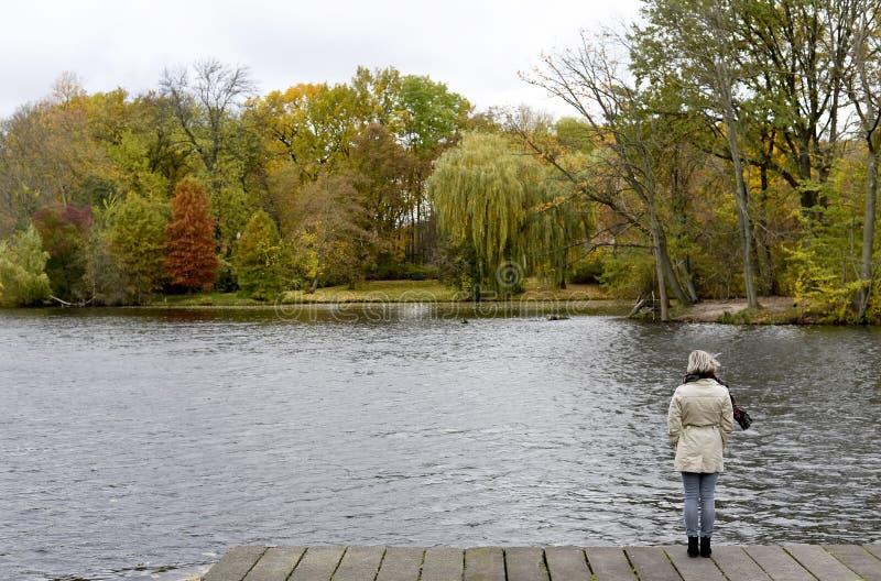 站立在湖的孤独的妇女 免版税库存照片