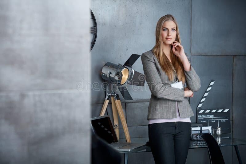 站立在演播室的年轻女实业家 图库摄影
