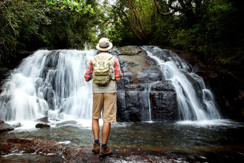 站立在瀑布前面的远足者 库存照片