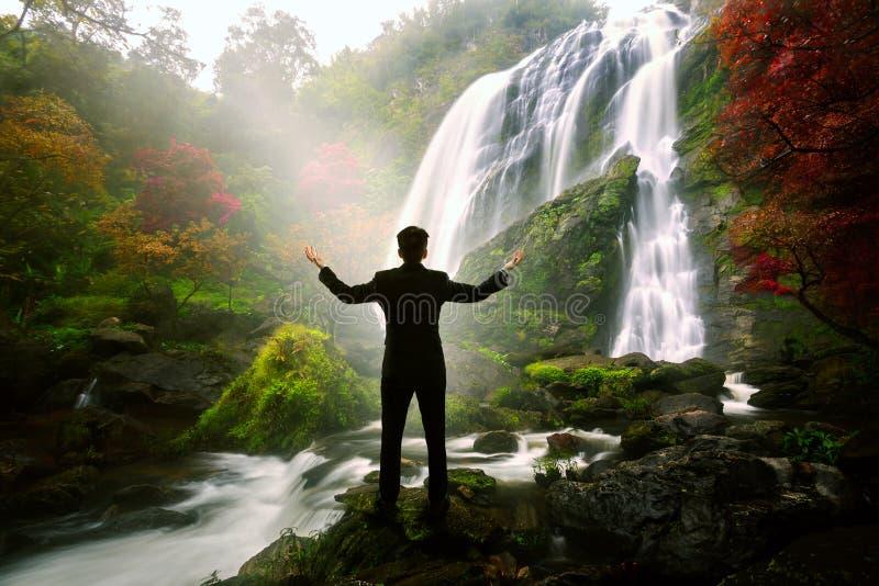站立在瀑布的松弛商人 图库摄影