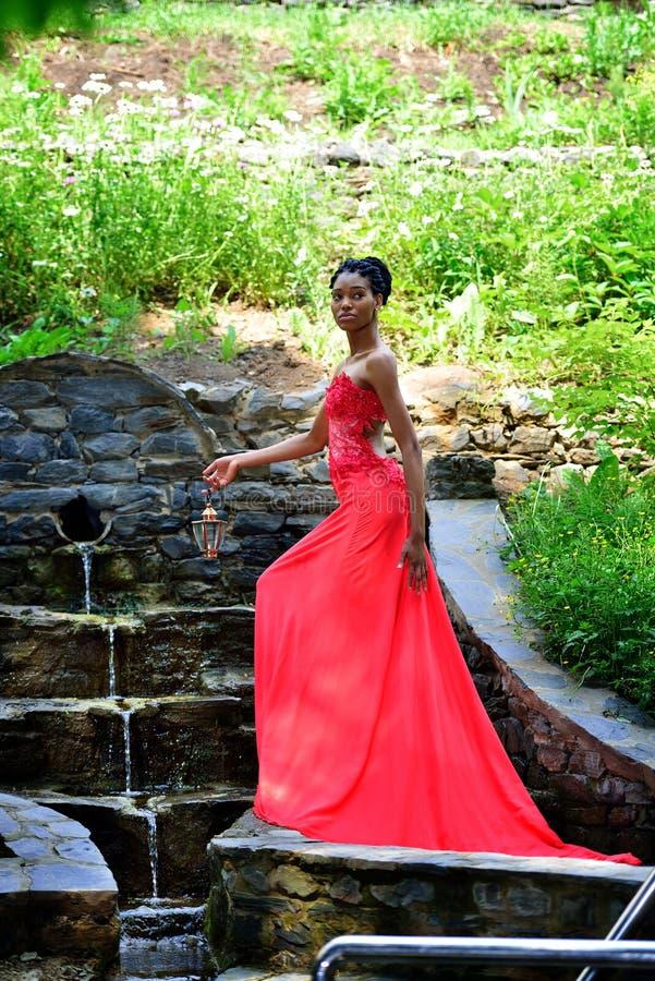 站立在瀑布的非洲女孩 免版税图库摄影
