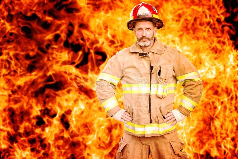 站立在火前面墙壁的消防员  免版税库存照片