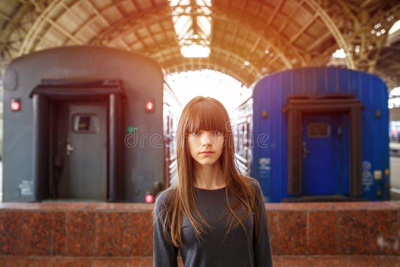 站立在火车站的一名美丽的妇女的画象在火车附近 免版税库存图片