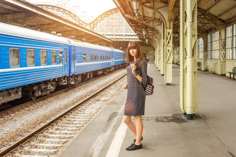 站立在火车站的平台的美丽的少妇 免版税库存图片