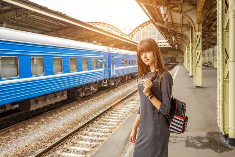站立在火车站的平台的美丽的少妇 免版税库存照片