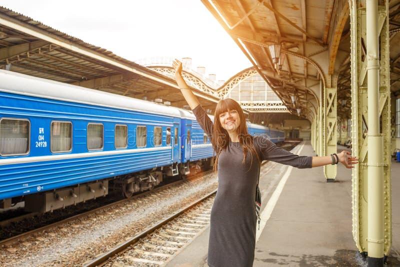 站立在火车站的平台的美丽的少妇 库存照片