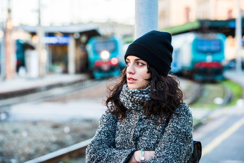 站立在火车站附近的女孩审判对阻止她泪花-侧视图 免版税库存图片