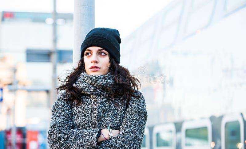 站立在火车站附近的美丽的女孩审判对阻止她泪花-接近的在最前面的看法 免版税库存照片