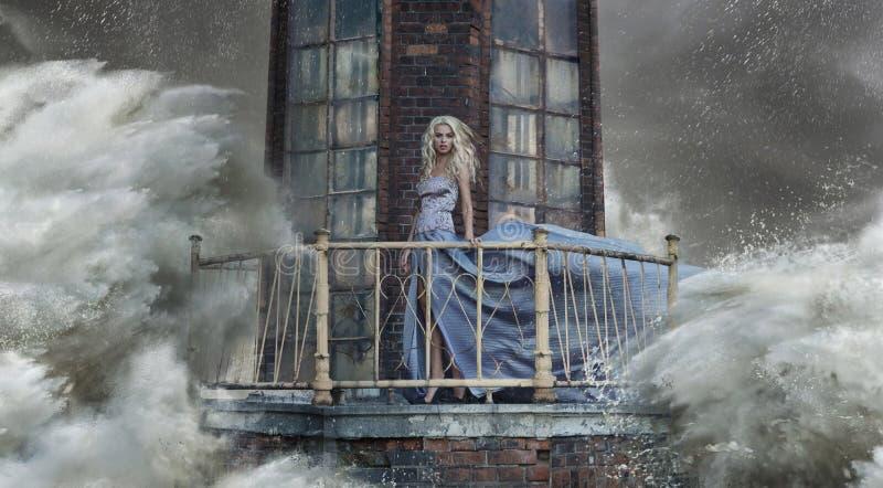 站立在灯塔的妇女的概念性照片 免版税库存图片