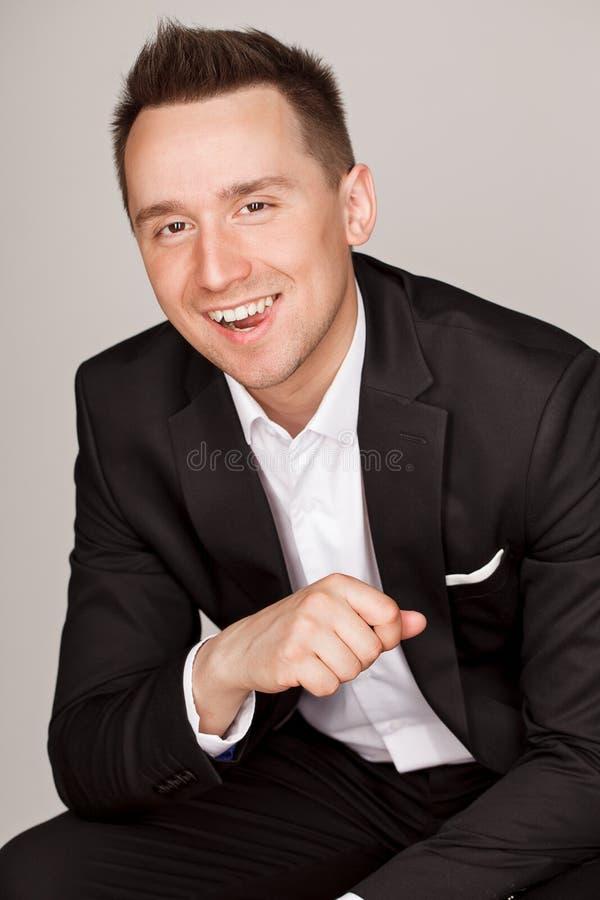 站立在灰色背景前面的一个确信的典雅的英俊的年轻人在穿着好的衣服的演播室 库存照片