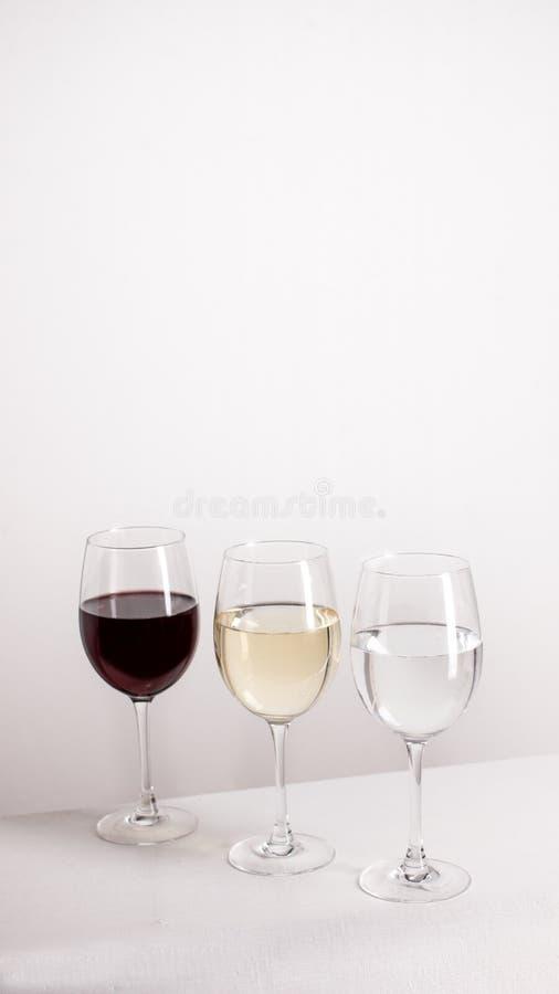 站立在灰色背景的一条线的三杯红色、白酒和水 免版税库存照片