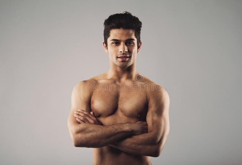 站立在灰色背景的胸部赤裸的肌肉人 库存照片