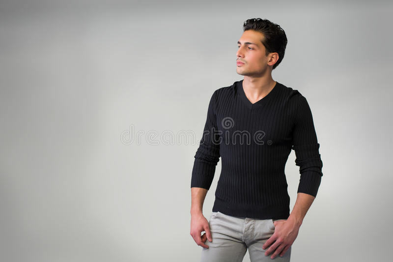 站立在灰色背景的英俊的拉丁年轻人。 免版税库存照片