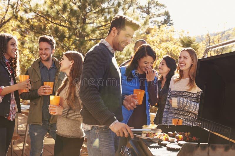 站立在烤肉,一烹调在格栅的小组朋友 免版税图库摄影