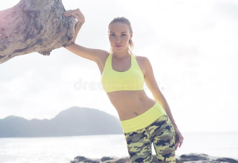 站立在热带海滩的年轻人相当白肤金发的女性佩带的锻炼衣物在海附近 免版税库存图片