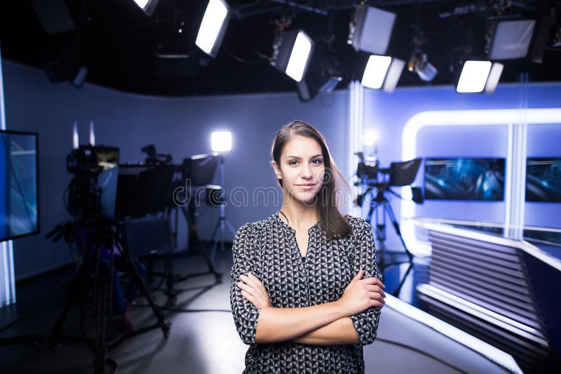 站立在照相机旁边的演播室的年轻美丽的深色的电视主持人 编辑的电视主任在演播室 免版税库存图片
