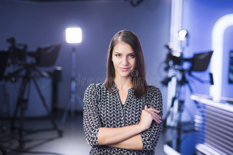 站立在照相机旁边的演播室的年轻美丽的深色的电视主持人 编辑的电视主任在演播室 免版税图库摄影