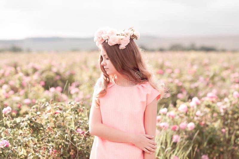 站立在玫瑰园里的十几岁的女孩 免版税图库摄影