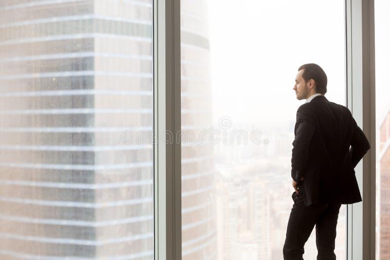 站立在现代办公室的严肃的年轻商人,看  免版税库存照片