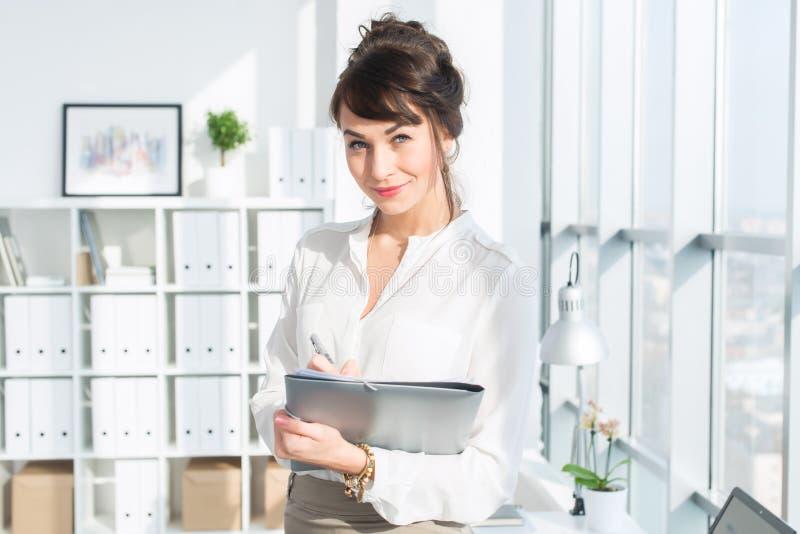 站立在现代办公室的可爱的雄心勃勃的女实业家,拿着纸文件夹,看照相机,微笑 免版税库存照片