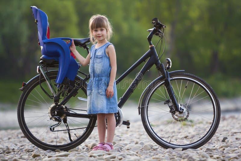 站立在现代自行车前面的小卵石的蓝色礼服的小相当白肤金发的女孩有在被弄脏的绿色树backgr的儿童位子的 库存照片