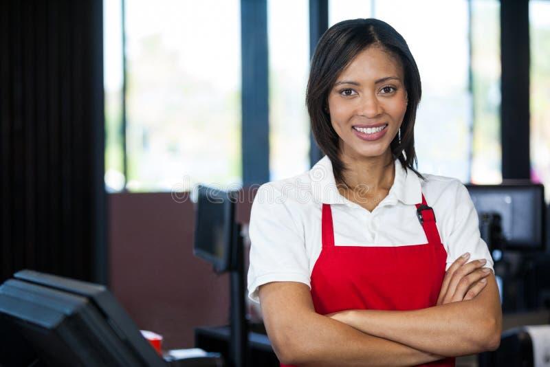 站立在现金柜台的女职工 免版税库存图片