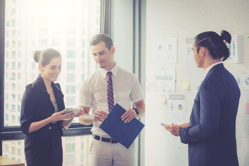 站立在现代办公室的三买卖人谈话在会议室 免版税库存图片