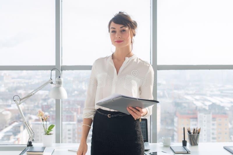 站立在现代办公室的可爱的雄心勃勃的女实业家,拿着纸文件夹,看照相机,微笑 图库摄影