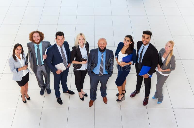站立在现代办公室顶视图,行的买卖人的商人小组愉快的微笑 免版税图库摄影