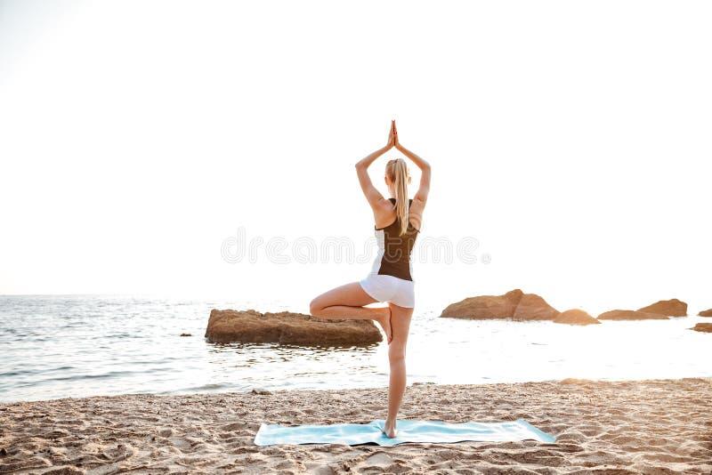 站立在瑜伽姿势的后面观点的妇女 免版税库存图片