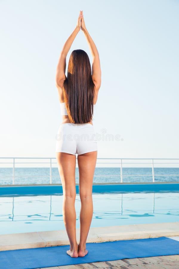 站立在瑜伽姿势的女孩的后面看法画象 库存图片