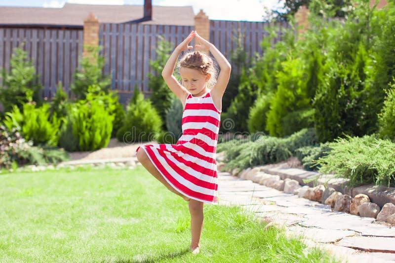 站立在瑜伽姿势的小可爱的女孩  库存图片