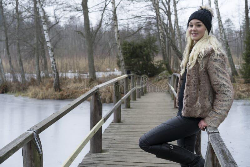 站立在瑞典冬天风景的桥梁的美丽的斯堪的纳维亚白肤金发的少妇 愉快微笑 库存图片