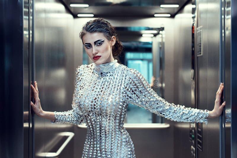 站立在电梯的银色未来派服装的年轻网络妇女 免版税库存照片