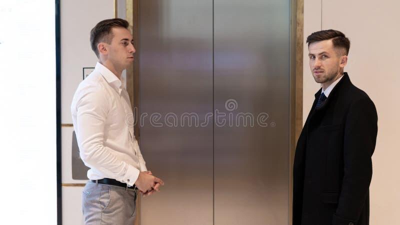 站立在电梯附近的两个商人 在一个电梯附近的商人在办公室 库存图片