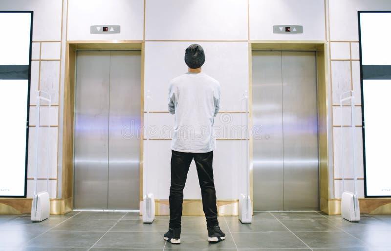 站立在电梯附近的帽子的人 库存图片