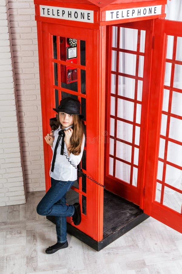 站立在电话亭旁边的小女孩 免版税图库摄影
