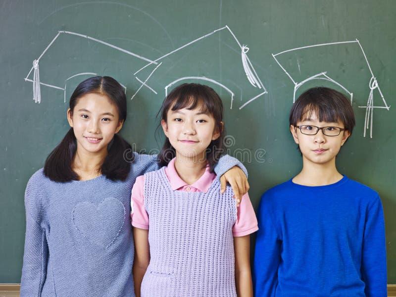 站立在白垩画下的亚裔小学学生 库存照片