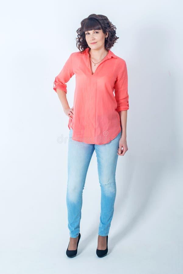 站立在白色墙壁前面的美丽的年轻时髦的女人 免版税库存照片
