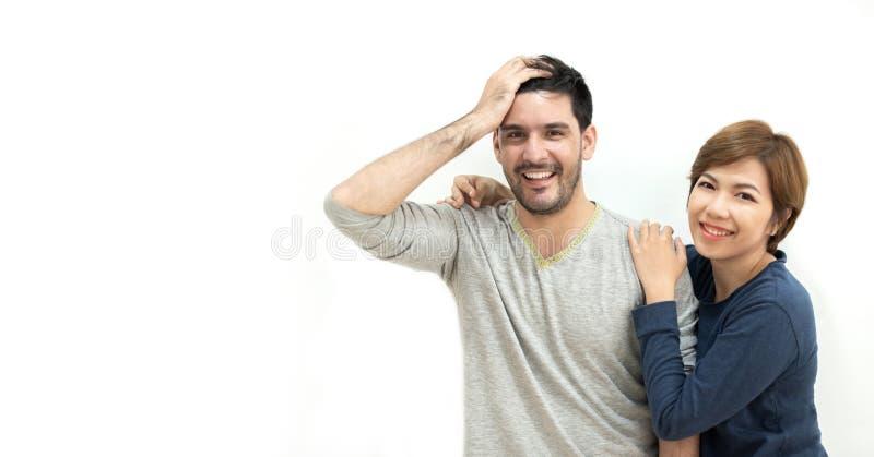 站立在白色墙壁的愉快的年轻夫妇画象  微笑和查看照相机 免版税图库摄影