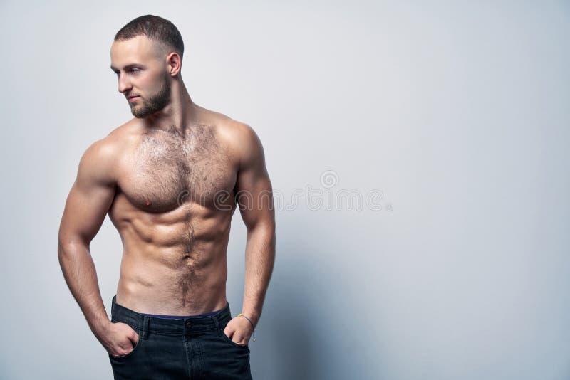 站立在白色墙壁的牛仔裤的肌肉赤裸上身的人 免版税库存图片