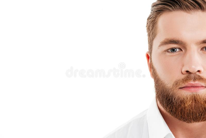 站立在白色墙壁的英俊的年轻有胡子的人 免版税库存照片