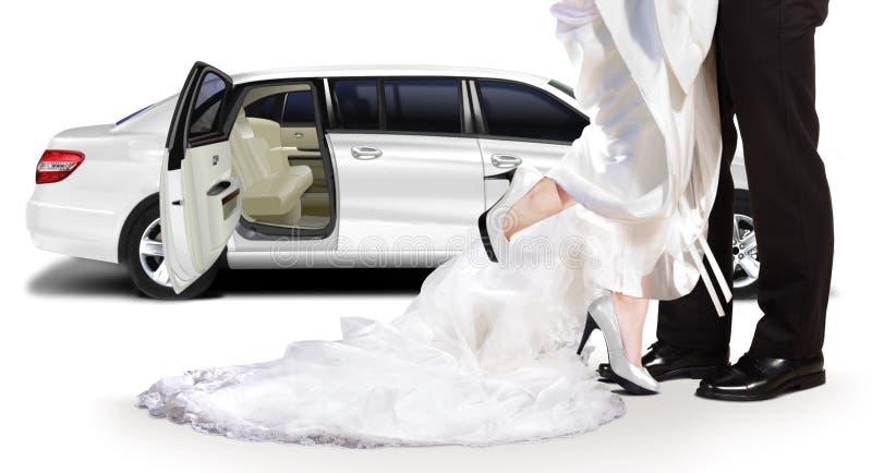 站立在白色大型高级轿车旁边的新郎和新娘 图库摄影